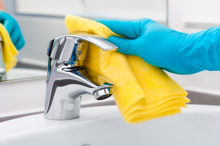 Woman doing chores in bathroom, cleaning tap