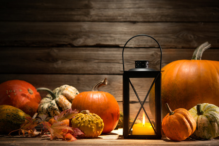 Lantern with candle, pumpkins and autumn decorations on old wooden