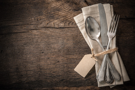 Vintage silverware with an empty tag on rustic wooden background