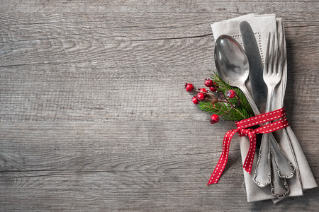 Christmas table place setting with christmas pine branches,ribbon and bow. Christmas holidays background