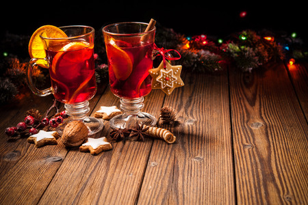Two glasses of hot mulled wine with oranges and spices