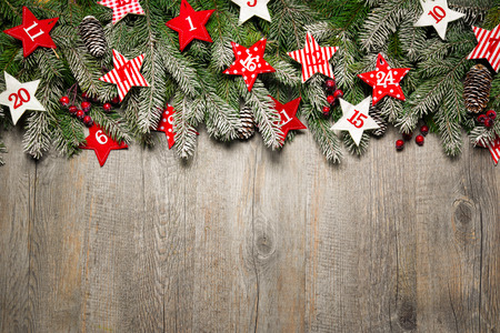 Fir tree  branches and advent calendar stars on old wooden board