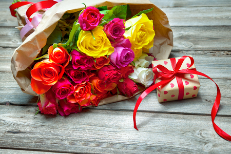 Background with bouquet of roses and gift box on wooden board