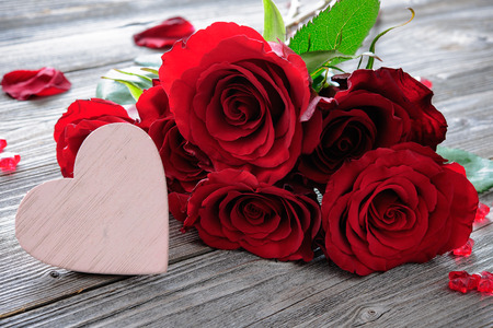 Red roses and heart on wooden background. Valentines day background