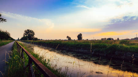 Empty cycling path along the Naviglio Pavese, canal at sunset. The canal stretches for 30km from Pavia to Milan in Lombardy, northern Italy