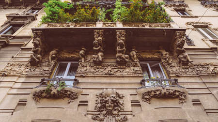 Facade of building in Porta Venezia neighbourhood. Ornamental humanist statues hanging from the wall. Architecture is early 1900s nature inspired Liberty, art-noveau style