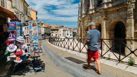 Tourists pass souvenir shops next to the Arenes dArles, Roman Amphitheater