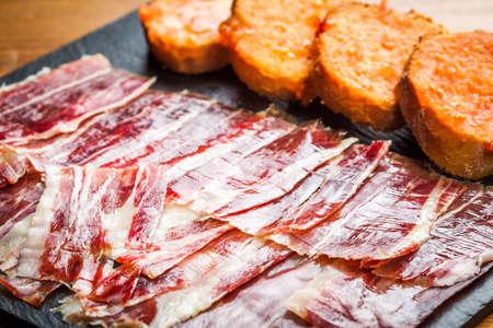 Spanish jabugo ham with bread and tomato.