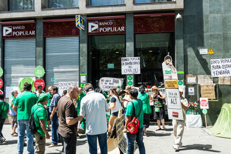 BARCELONA, SPAIN - 2 JULY: People protests in front of Banco Popular in Passeig de Gracia in consequence of the grave economy crisis, Barcelona. July 2, 2013.