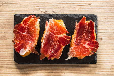 Jamon iberico, the best spanish ham tapas. Top view on a wooden table.