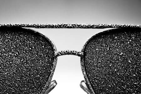 Photo pour Sunglasses with artificial snow on white-purple background close-up view. Monochome black and white image. - image libre de droit