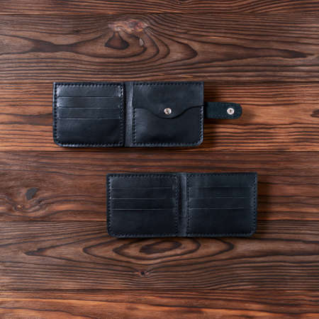 Photo pour Two black handmade leather wallets on wooden textured background. Up to down view. Wallet stock photo. - image libre de droit