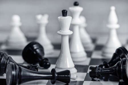 Photo pour The concept of team success and corporate spirit. White chess pieces on the chessboard Around them lie the defeated black pieces. - image libre de droit