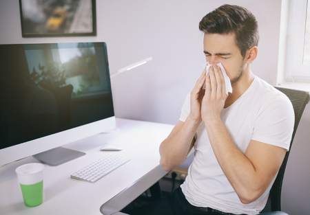 Photo for Side view of the patient's employer. sneezing into a tissue in an office near the window in the computer. Freelancer designer with a cold - Royalty Free Image