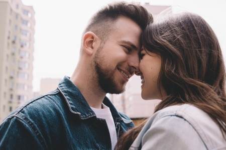 Happy attractive young couple in jeans jackets standing among buildings and trying too kiss each other. They are so delighted to have such moments. Close up