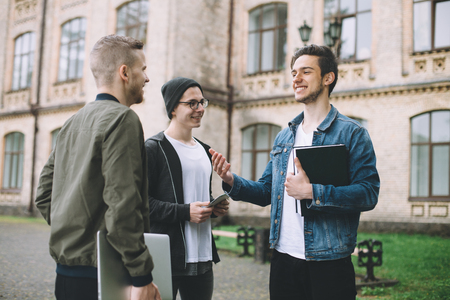 Happy and cheerful friends standing near university and laughing at somebodys joke. They are discussing their free time after the studying