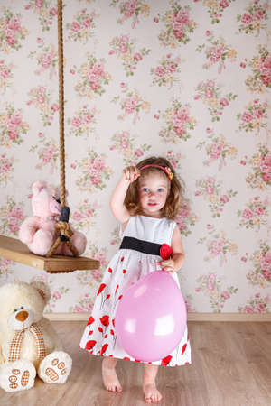 little girl in a beautiful dress near a swing in studio, there are two teddy bear sitting on the swing. girl holding a pink balloon