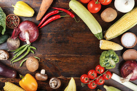 vegetable background - corn, beet, cherry tomatoes, mushrooms, eggplant, zucchini - on a dark brown wooden background place for text
