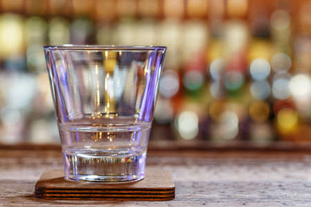 Empty glass on a wooden worn background of a bar, on a blurry background of bottles with alcohol