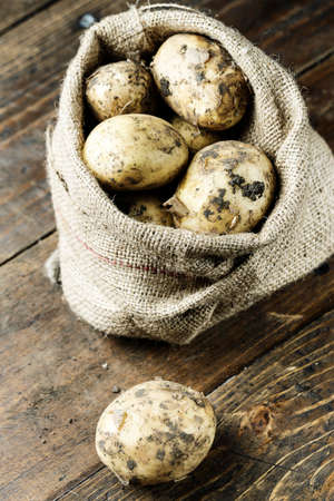 lot of young potatoes in a sackcloth sack on a wooden background