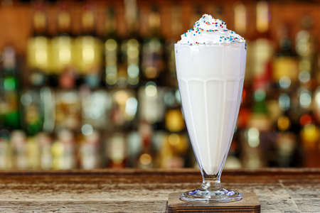Non-alcoholic milkshake with whipped cream on the bar in a cafe or restaurant. Space for text