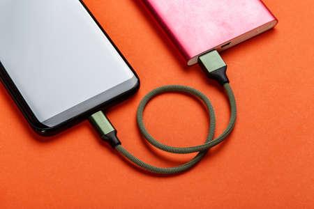 Photo pour Smartphone charging with power bank on color background - image libre de droit