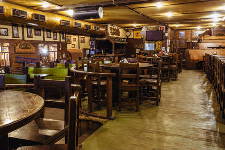 Photo pour Kiev, Ukraine-March 19, 2018. Traditional Irish beer pub with a wooden interior. many empty tables and chairs. - image libre de droit
