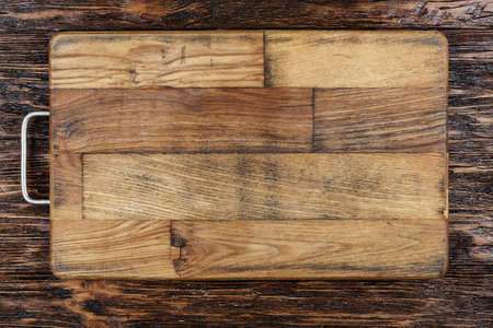 Photo pour Rectangular cutting wooden board on a brown wooden background. place for text  - image libre de droit
