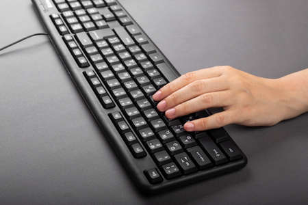 Photo for female hand on a black computer keyboard. girl is typing on computer  - Royalty Free Image
