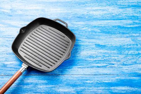 Photo pour New cast-iron grill pan on a wooden background. place for text  - image libre de droit