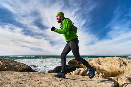 Photo pour Athlete guy runs along the seashore on a sunny day. Trail Running. Mangystau Peninsula. Kazakhstan - image libre de droit
