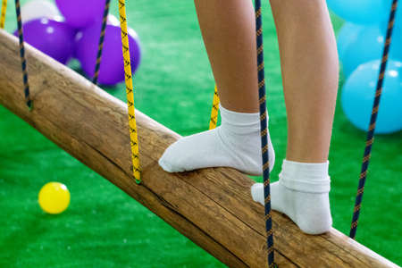 Children's feet  at the playground with swinging bridge.