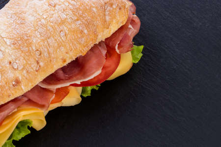 Photo pour Ciabatta sandwich with lettuce , prosciutto and  cheese over stone background. Top view with copy space. - image libre de droit