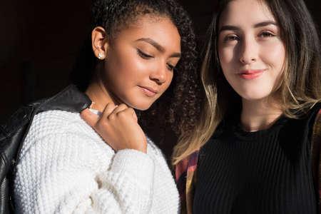 Foto de Portrait of two beautiful fashionable Hispanic girls, happy smiling posing for the camera. Autumn street art photo. Background to the autumn sale. fashion photography. - Imagen libre de derechos