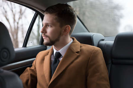 portrait of a young guy with a beard. A businessman in a car in the passenger seat rides to the office, to work. Businessman 30 years old. in a suit and a white shirt with a tie. Business style. Businessman man rides in a car