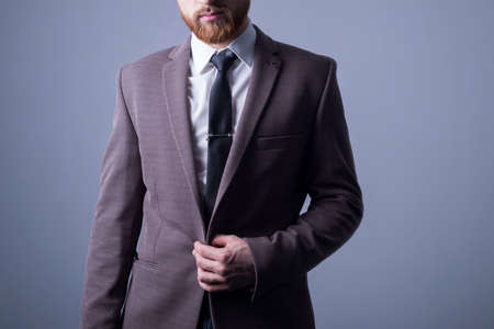 Photo pour studio portrait of a young bearded handsome guy of twenty-five years old, in an official suit, buttoning a button in a jacket. On a dark background. Dramatic light. Official style. Office Style. Fashion and office - image libre de droit