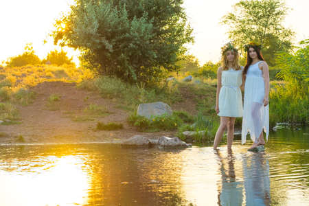 Photo pour two girlfriends, young girls in white dresses and flower wreaths on their heads, standing in a river of water, near the shore, laughing, against the setting sun. The concept of virginity - image libre de droit