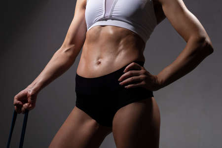 Photo for studio portrait of a female athlete, with a flawless athletic body. hand straining fitness gum. On a gray background Attractive brunette sportswoman with perfect figure determined with result using expander training upper body, slim girl in blue active wear motivated with fitness goals having pilates workout in gym - Royalty Free Image