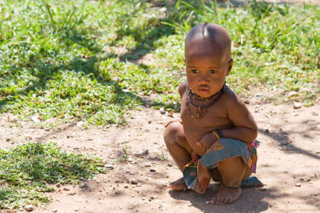 Cute Himba boy sitting in shade and looking away