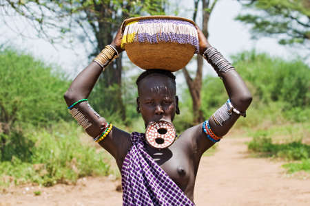 OMO VALLEY, ETHIOPIA - MARCH 13, 2010: An unidentified woman of the Mursi tribe with traditional ornaments and lip plate carries a basket on her head in the Omo valley, Ethiopia.