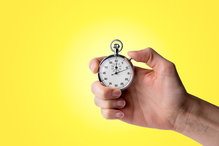 Foto de timer hold in hand, pressed button - yellow background - Imagen libre de derechos