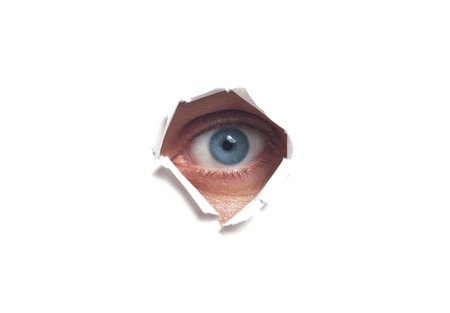 Human eye, seen through a hole in the wall isolated