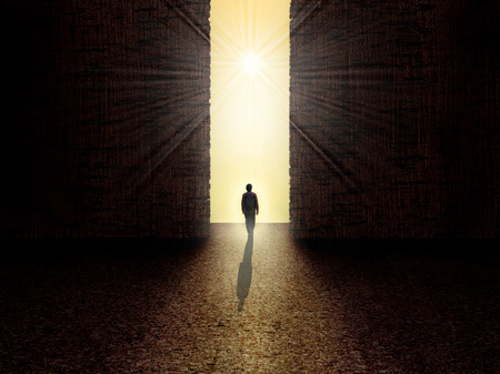 Photo for Man walking towards the light from darkness - Royalty Free Image