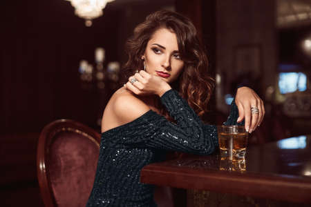Foto de Beauty young brunette woman sitting at the bar with glass of whiskey in luxury interior - Imagen libre de derechos