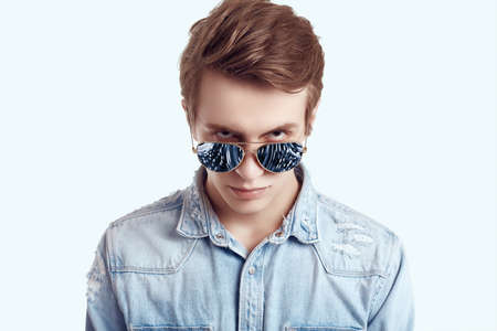 Photo for Portrait of handsome hipster man in fashion sunglasses wearing jeans jacket on white background in studio - Royalty Free Image