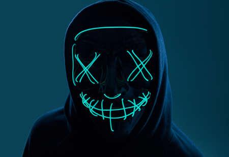 Photo pour Portrait of an anonymous man in a black hoodie hiding his face behind a scary neon mask. Studio shot. - image libre de droit