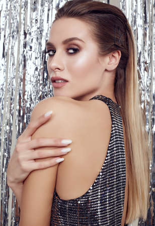 Photo pour Portrait of gorgeous elegant blonde woman with perfect body in luxurious silver sequin top posing on shiny tinsel background. Studio shot. - image libre de droit