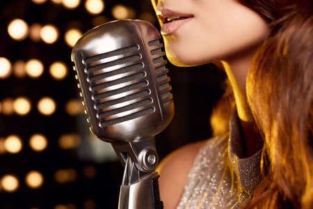 Photo pour Close-up portrait of gorgeous singer woman in elegant dress with retro microphone on restaurant stage spotlights background. - image libre de droit