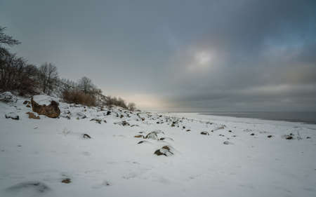 snowy rocky shore of the lake on the background of gray cloudy sky