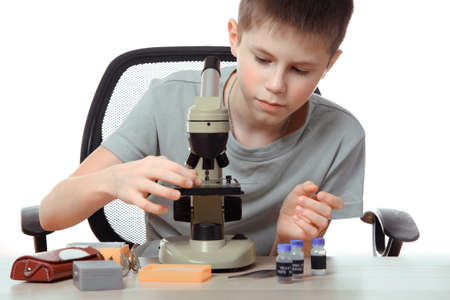 Teen boy in school laboratory. Researcher working with microscope